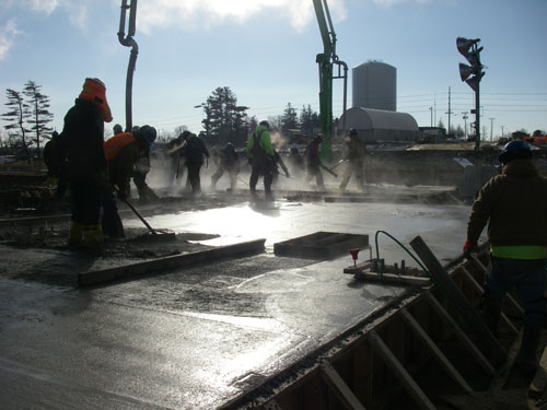 <b>Steam rises from a newly poured concrete slab at an industrial construction site. Carl A. Nelson & Company self-performs about 40 percent of contracted work annually, including substructure and superstructure concrete.</b>